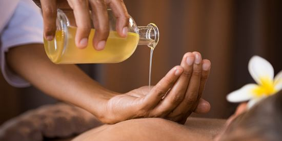 Massage oil is poured into hand in an relaxing environment