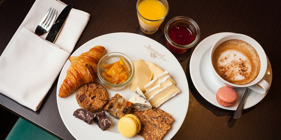 A rich breakfast platter consisting of a croissant, macarons, biscuits and marmelade. Cappuccino and organce juice on the side.