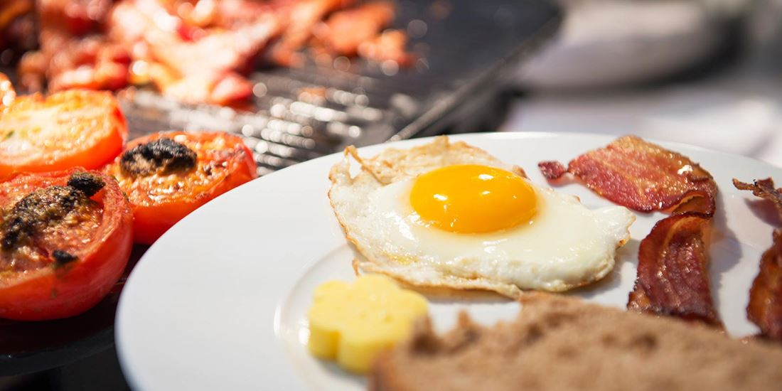 Detail image of a sunny side up fried egg, bacon, a piece of toast and ovenbaked tomatoes topped with pesto.