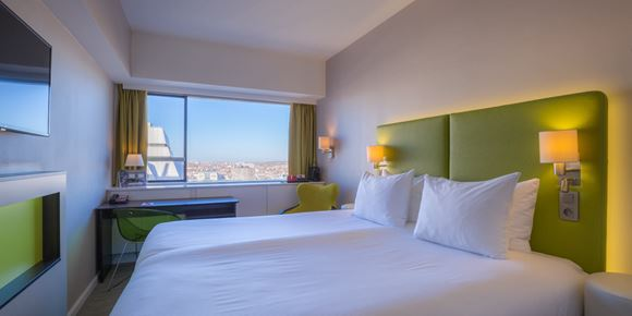 Double room in green design with white sheets and city view at Thon Hotel Brussels City Centre