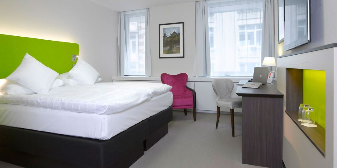 Desk, seating and a large bed in a double room at Thon Hotel EU