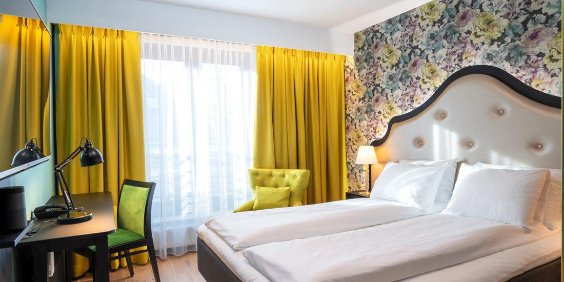 Blomstret tapet og dobbeltseng i dobbeltrom, gule gardiner, tv og arbeidsplass på Thon Hotel Cecil i Oslo sentrum