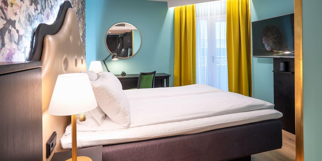 Blomstret tapet bak queen-seng i queen room med turkise farger og gule gardiner, tv og arbeidsplass på Thon Hotel Cecil i Oslo sentrum