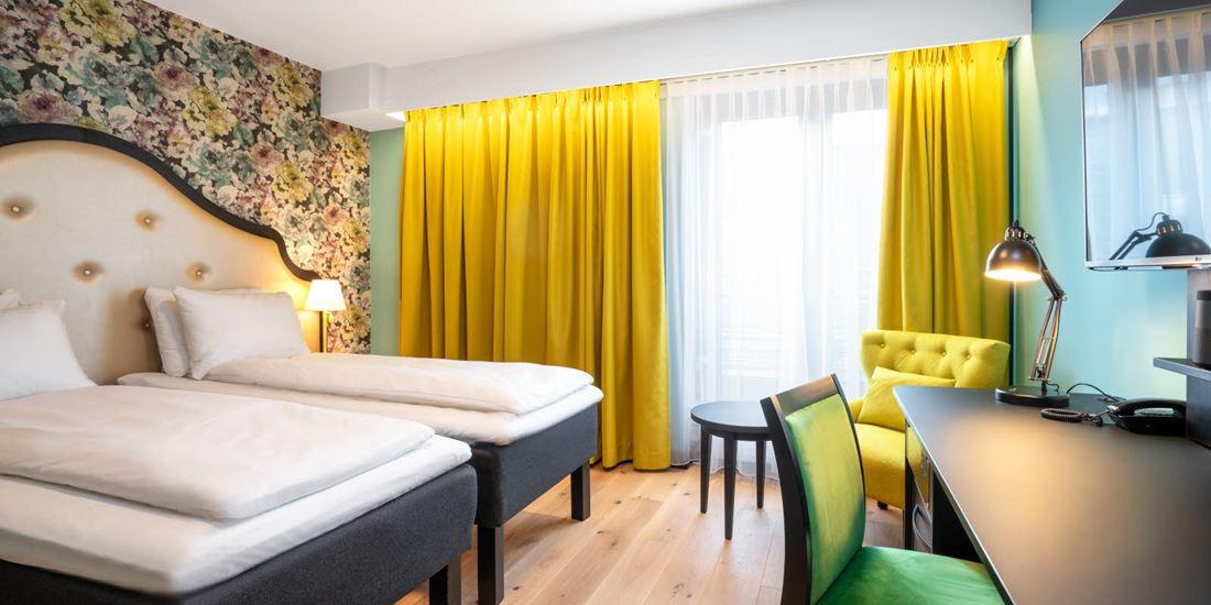 To enkeltsenger, blomstret tapet bak sengene, gul stol, arbeidspult og store vinduer med store gule gardiner på twin room på Thon Hotel Cecil i Oslo sentrum