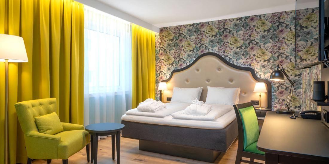 Blomstret tapet og stor dobbeltseng i superiorrom på Thon Hotel Cecil i Oslo sentrum
