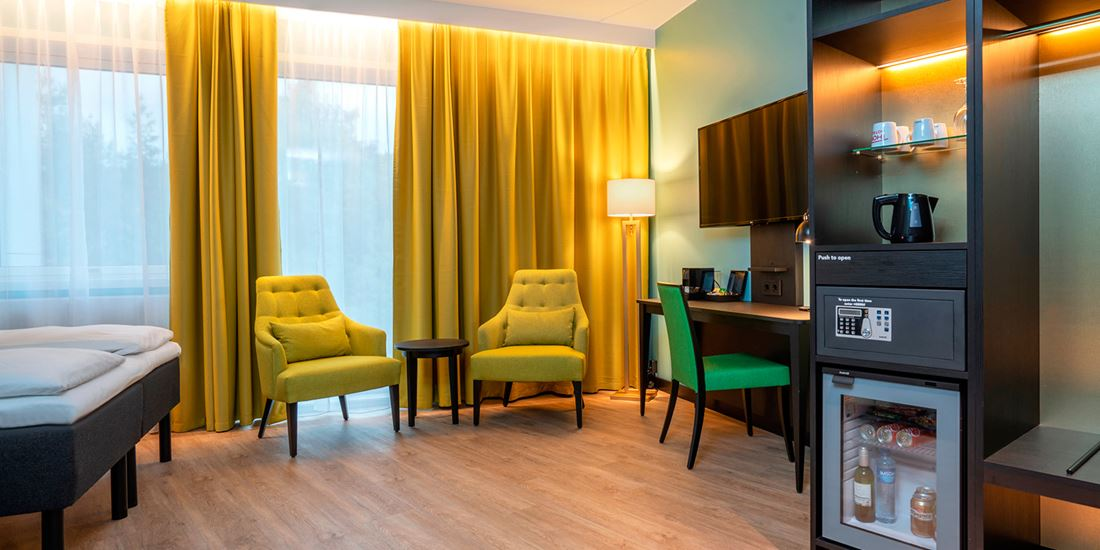 Seng, sittegruppe og skrivebord i business room på Thon Hotel Linne i Oslo