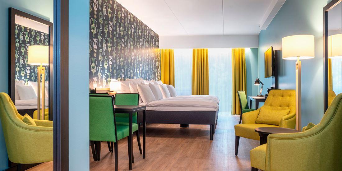 Stor seng, sittegruppe og spisebord i junior suite på Thon Hotel Linne i Oslo