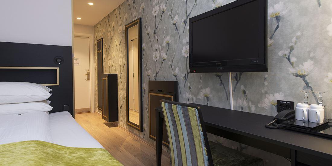 Seng og TV i lite enkeltrom på Thon Hotel Opera