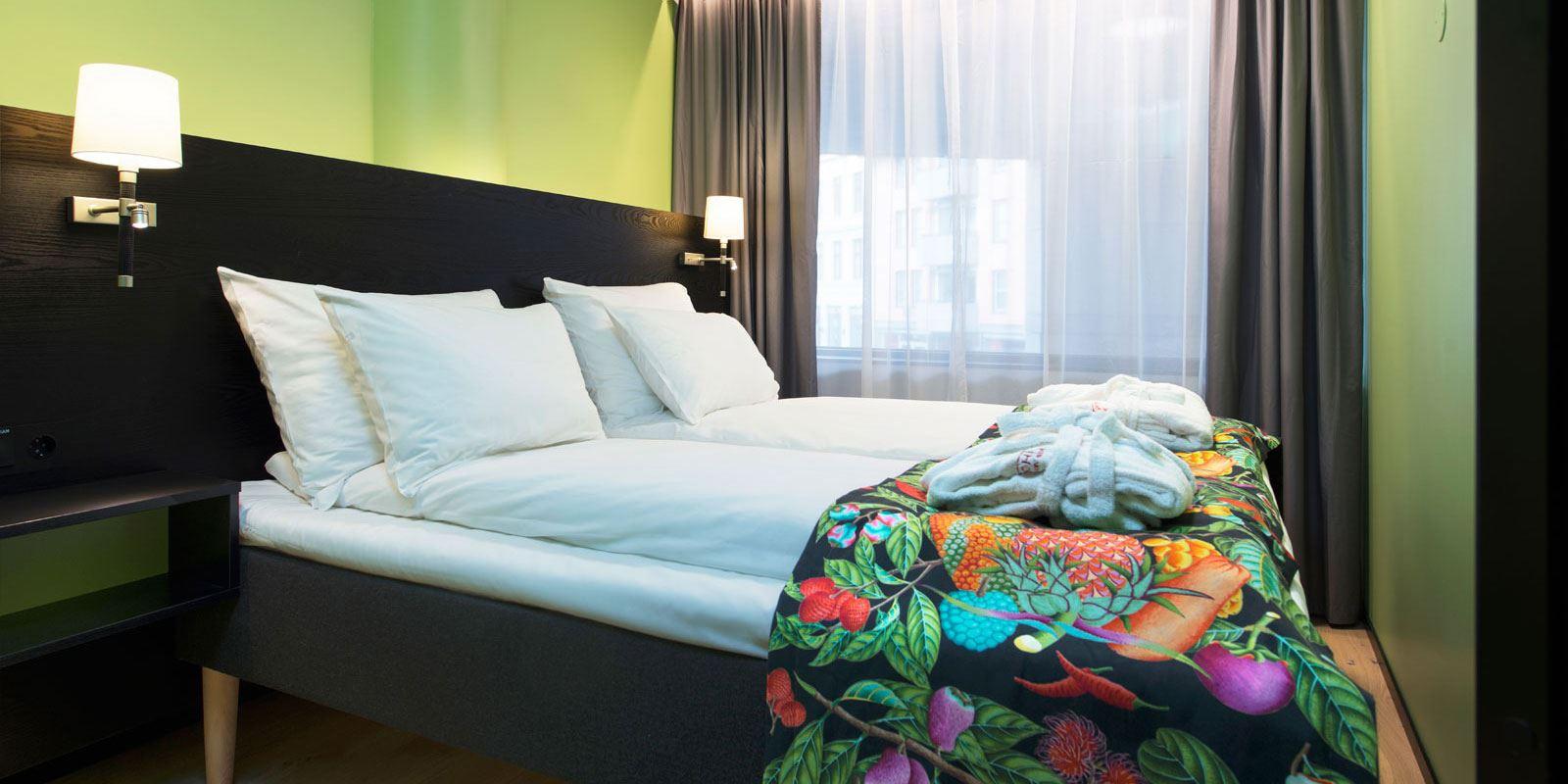 junior suite dobbeltseng, nattbord og nattbordslamper på hver side, sengeteppe, morgenkåper plassert pent sammenbrettet på enden av sengen, vindu med lystette gardiner