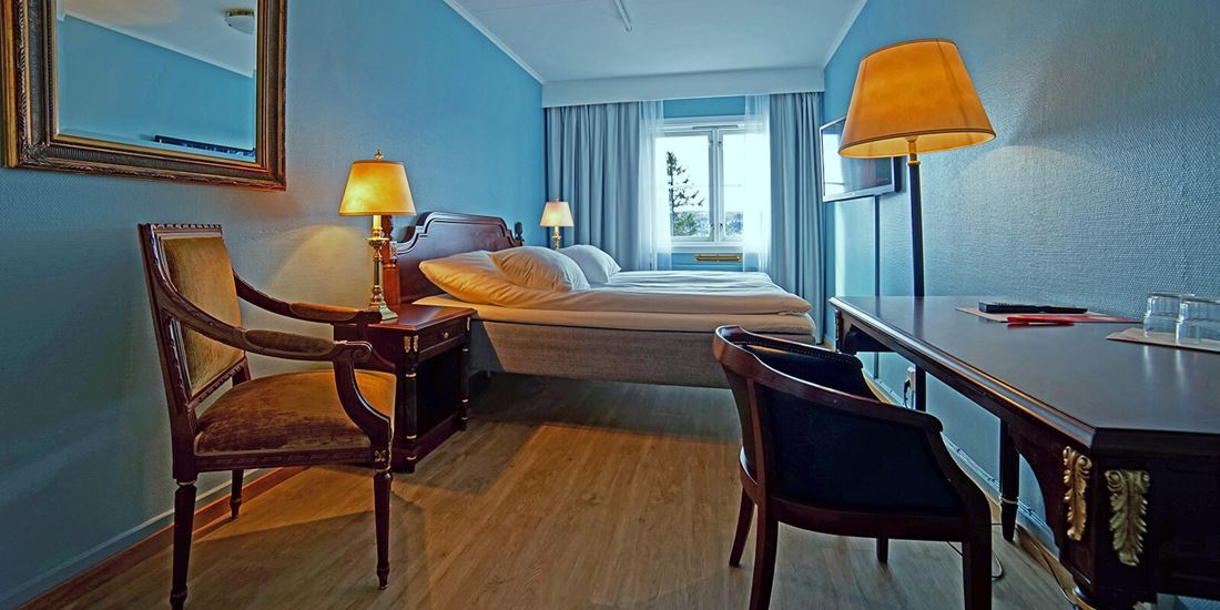 Bed, chair and desk in room at Thon Hotel Skeikampen