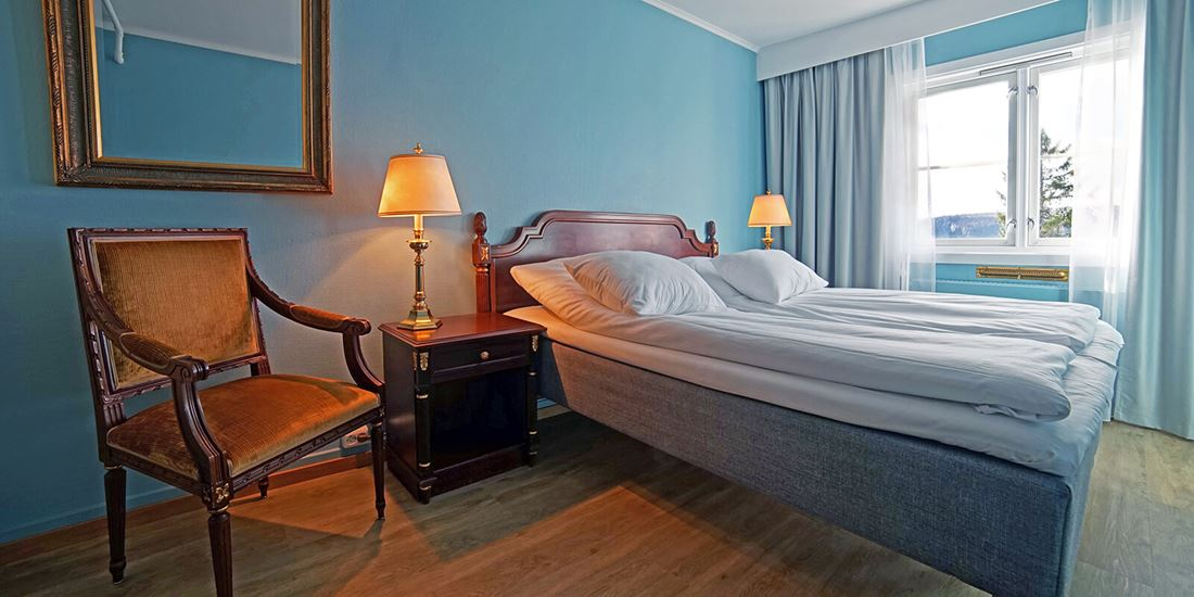 Bed and chair in room at Thon Hotel Skeikampen