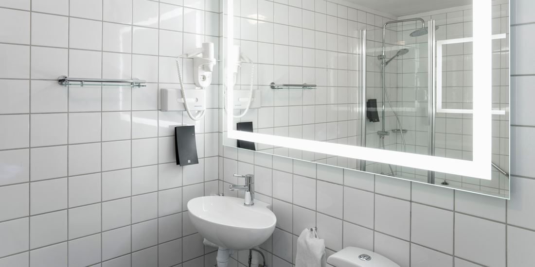 Bathroom with large mirror and wash basin in the family room and business room at Thon Hotel Skeikampen