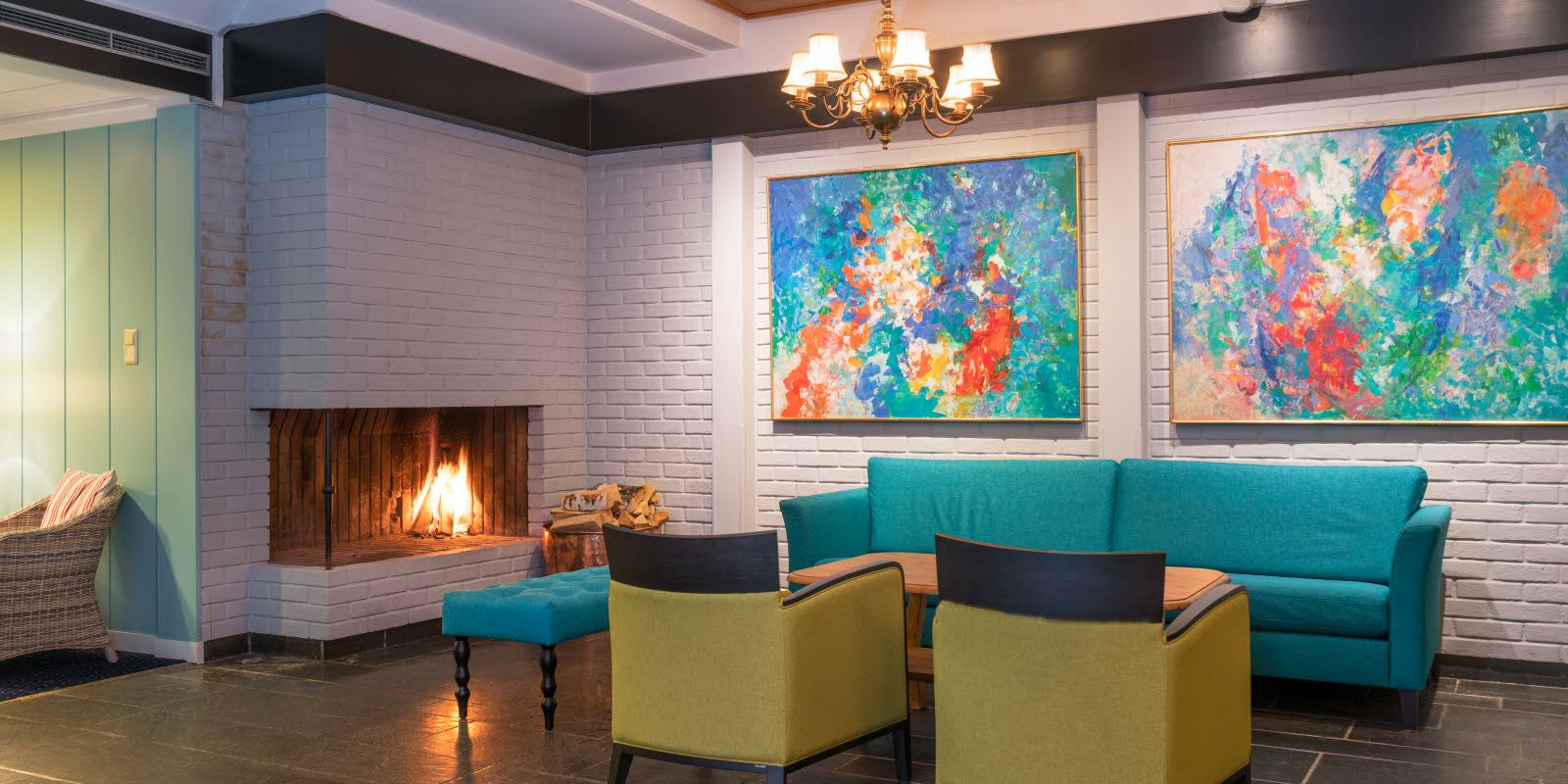 Lobby with seating area in fresh colours, fireplace and artwork on the walls of Thon Hotel Skeikampen