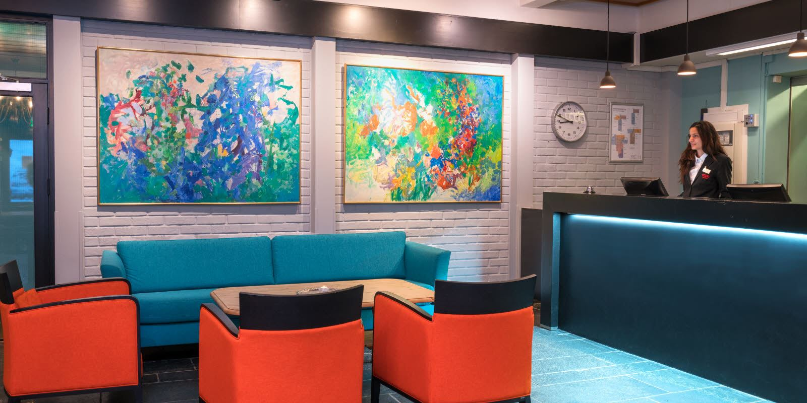 Staffed reception with sofa and seating areas and large abstract images on the wall with soft lighting at Thon Hotel Skeikampen