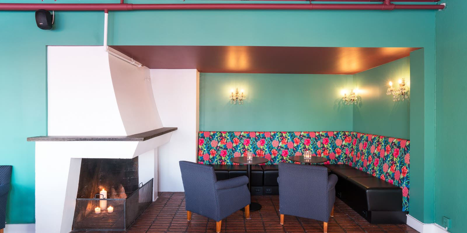 Lounge bar with fireplace and seating corner, patterned wallpaper above the seating area and turquoise walls at Thon Hotel Skeikampen
