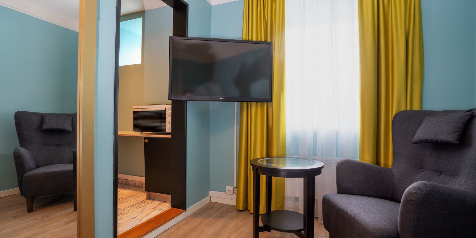 TV and seating area in Standard Single Room at Thon Hotel Linne Apartments