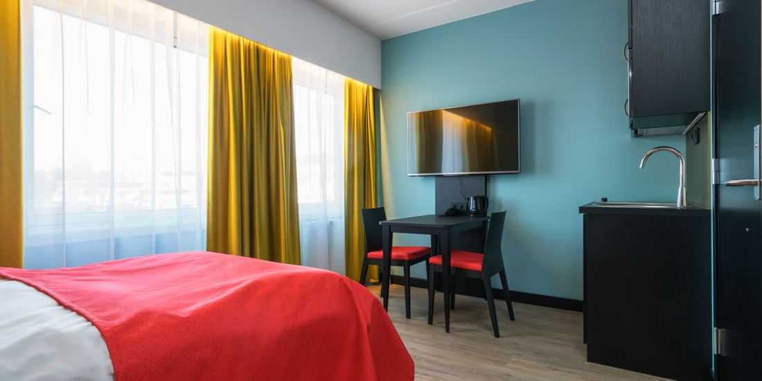 Tweepersoonsbed, smart-tv en keukentafel in eenpersoonsappartement van Thon Hotel Linne Apartments