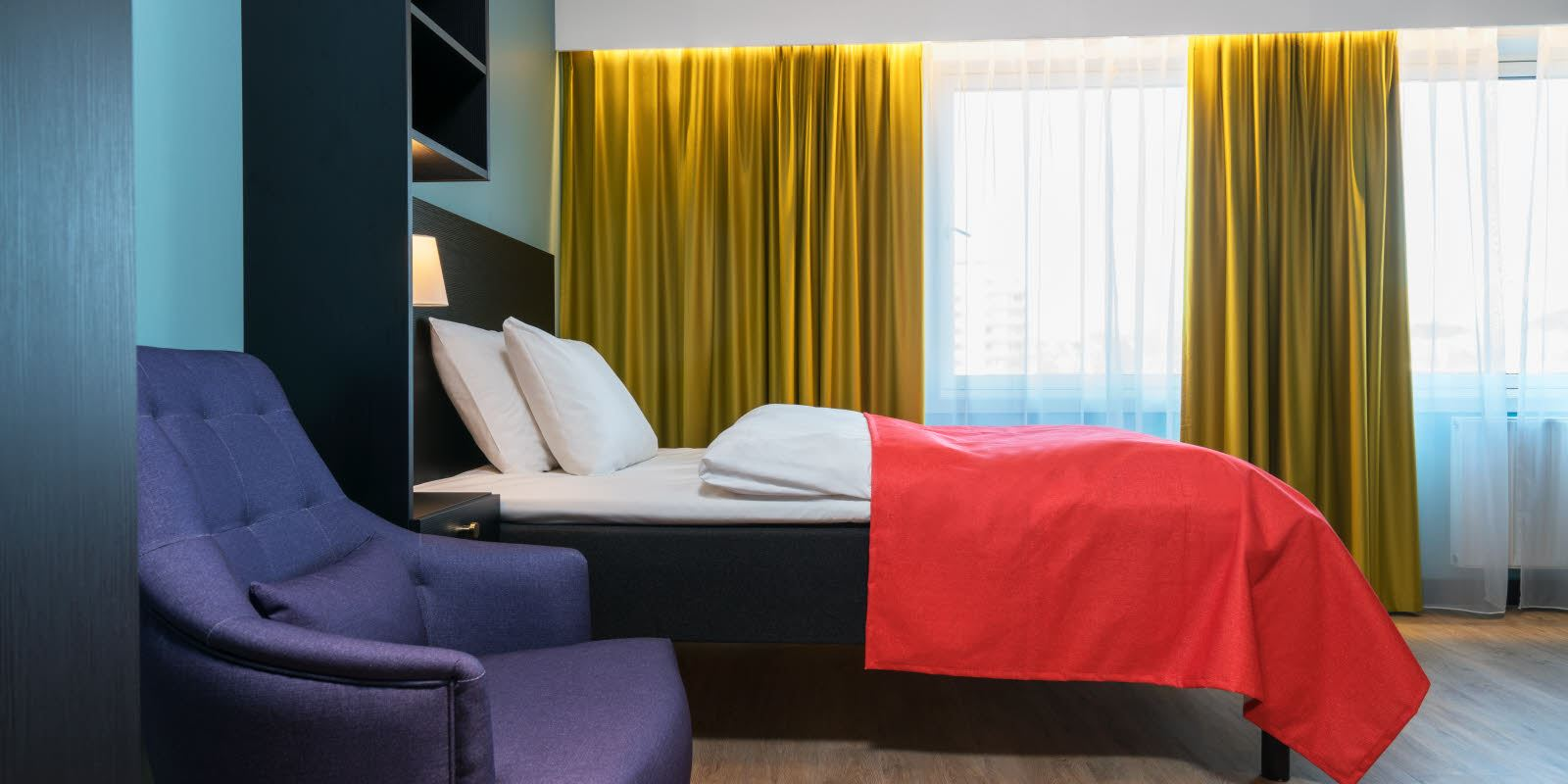 Double bed and blue armchair in 1-room apartment at Thon Hotel Linne Apartments