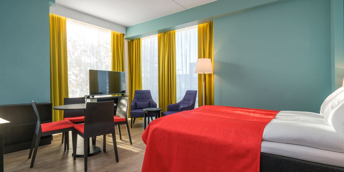 Tweepersoonsbed, smart-tv en keukentafel in tweepersoonsappartement van Thon Hotel Linne Apartments