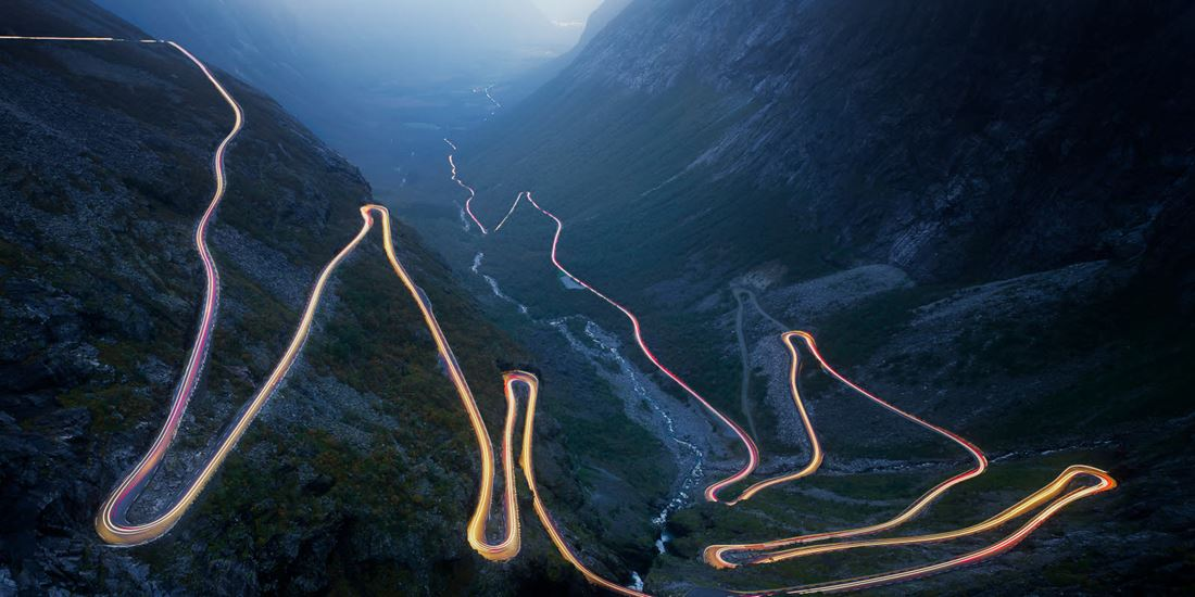 Tourist magnet Trollstigen illuminated by car lights