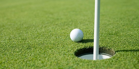 Close-up photo of a golf ball next to a golf hole