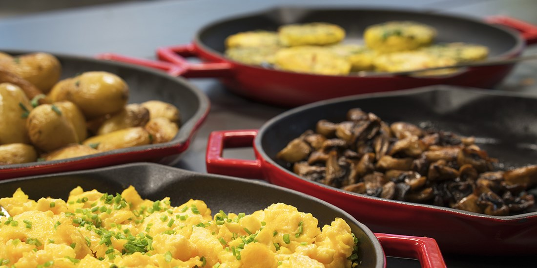 Pans with scrambled eggs, mushrooms, and potatoes
