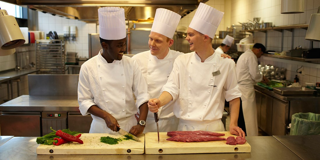 Two trainees receiving guidance from a head chef